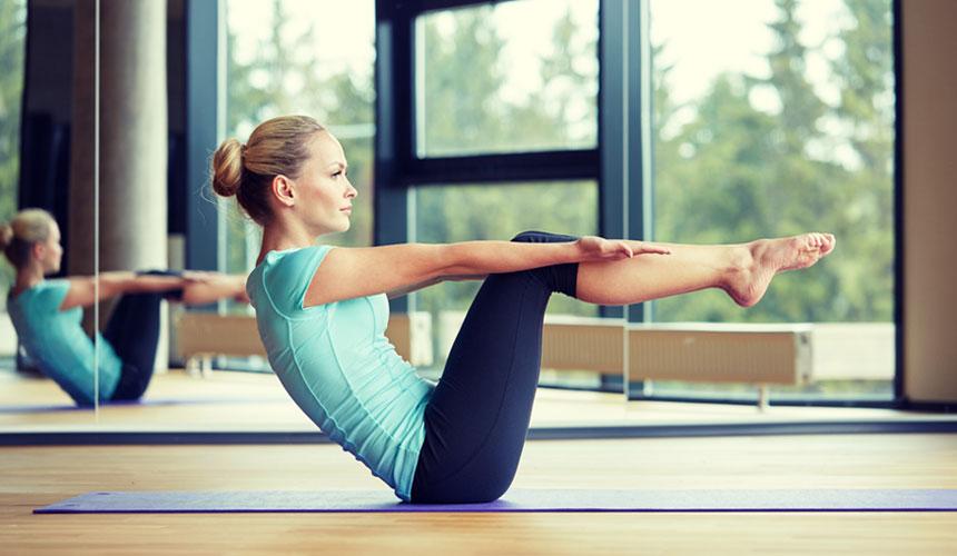 Девушка делает упражнения в зале с зеркалом