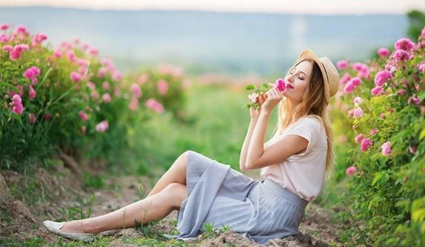Дівчина з квіткою сидить у полі з квітів