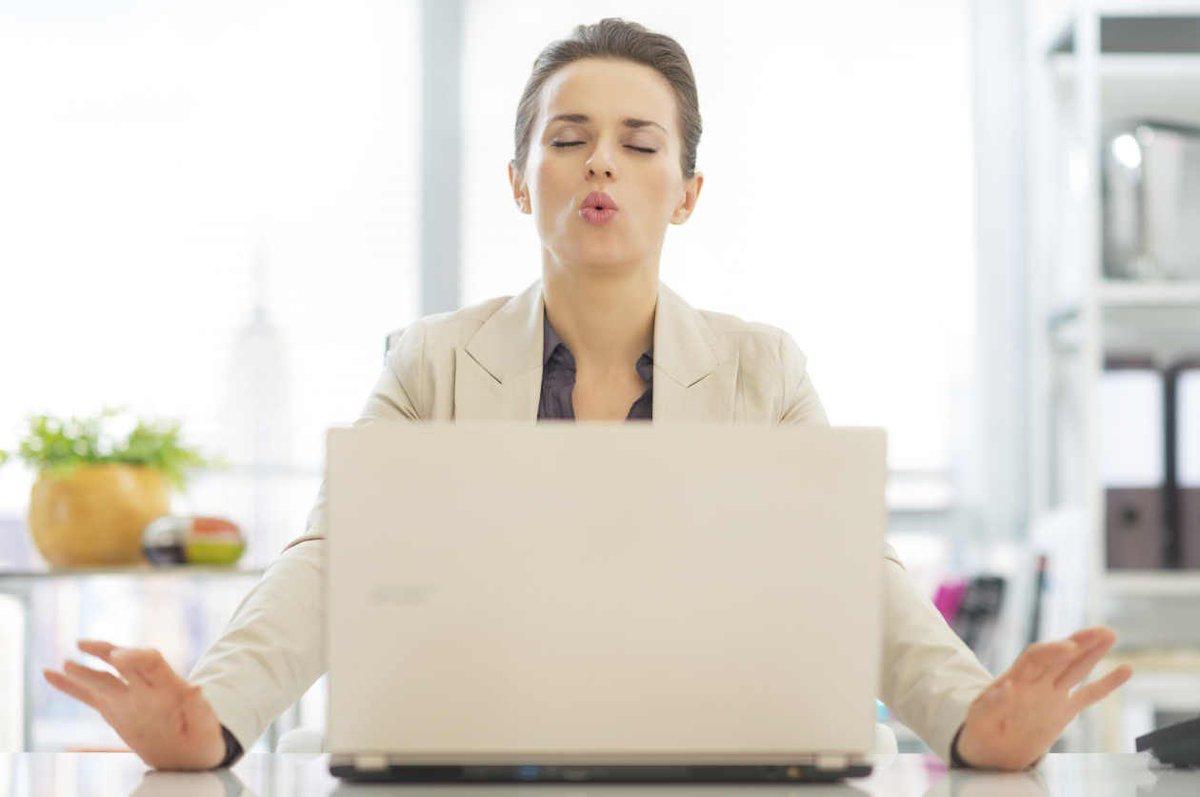 Девушка делает глубокий вдох за ноутбуком