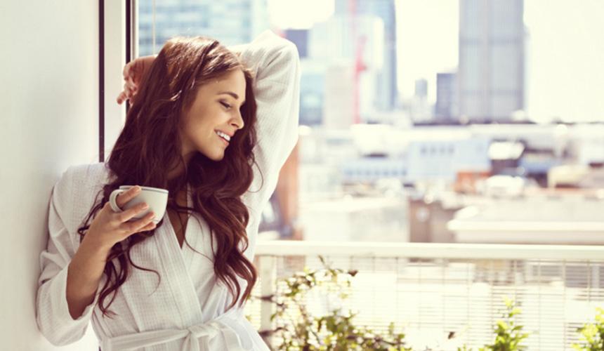 Дівчина з чашкою біля вікна