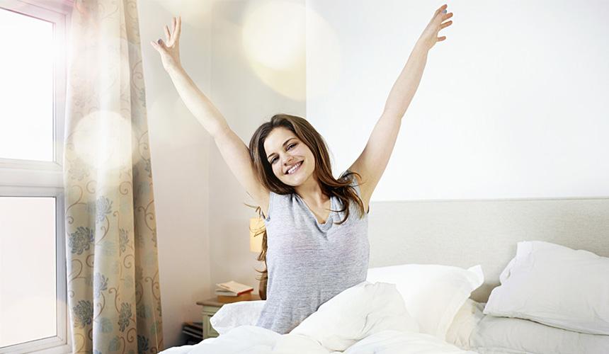 Девушка бодро потягивает руки в постели