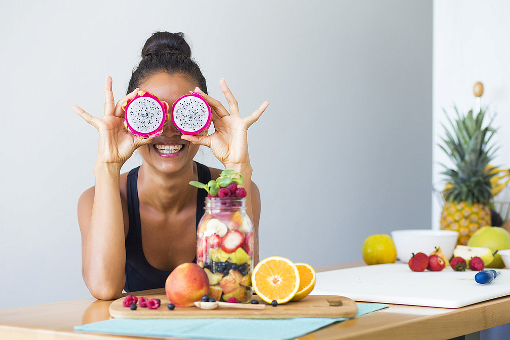 Девушка с разрезанной питахайей на глазах за столом, банка с фруктами и фрукты на столе