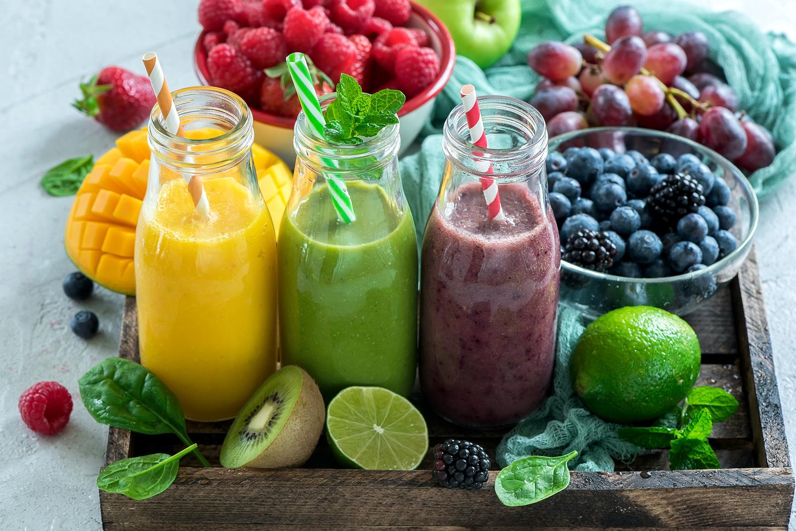 Различные смузи в бутылках с трубочкой и фрукты