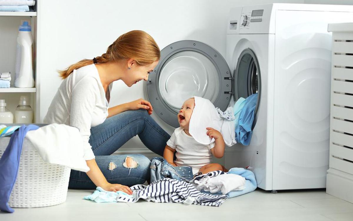 Дівчина з дитиною біля пральної машини.