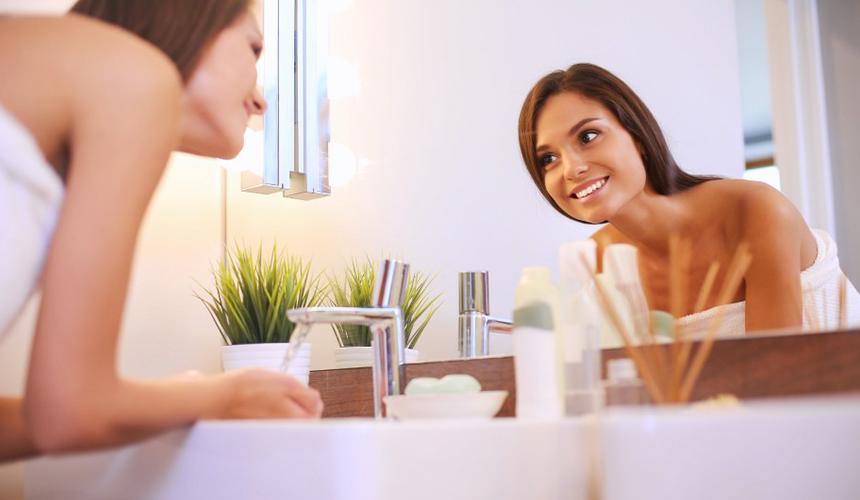 Девушка смотрит на себя в зеркало в ванной комнате