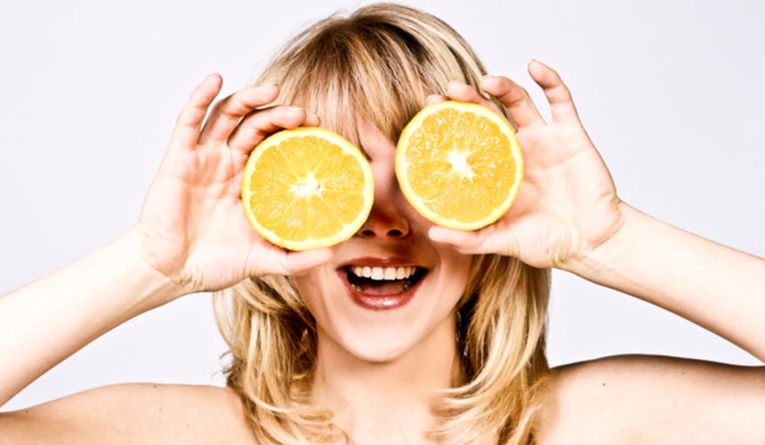 Дівчина тримає в руках розрізаний апельсин на тлі очей