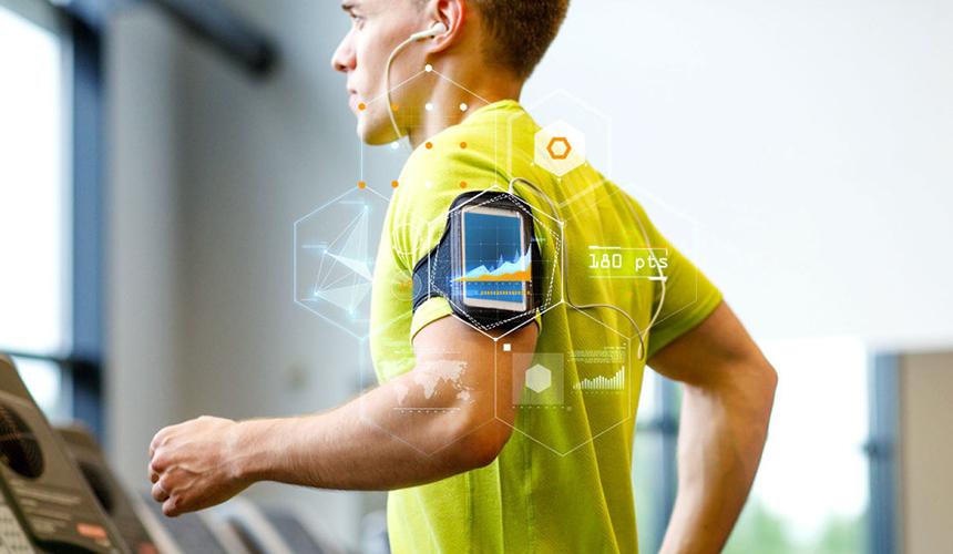 Хлопець на біговій доріжці з розумним годинником на предпліччі