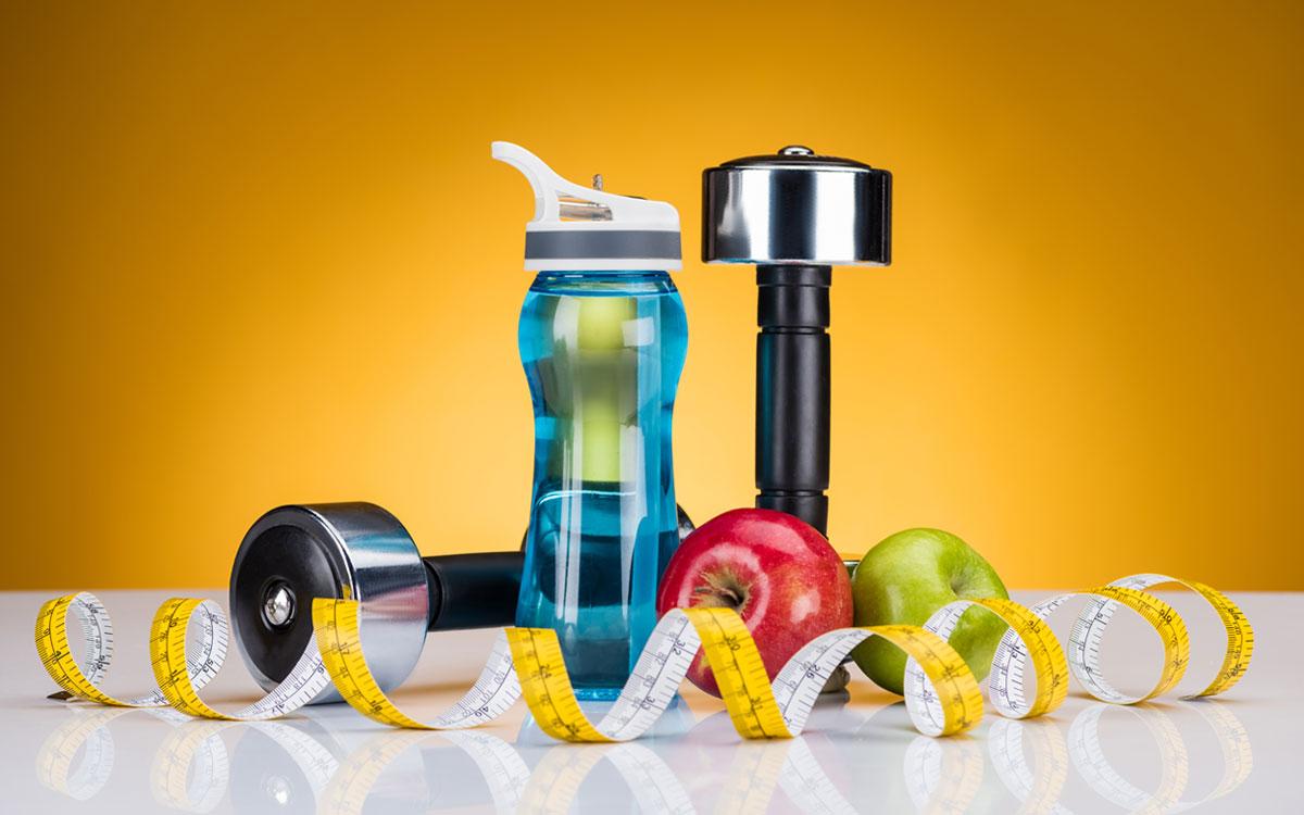 Пляшка для води, сантиметр, гантелі і яблука