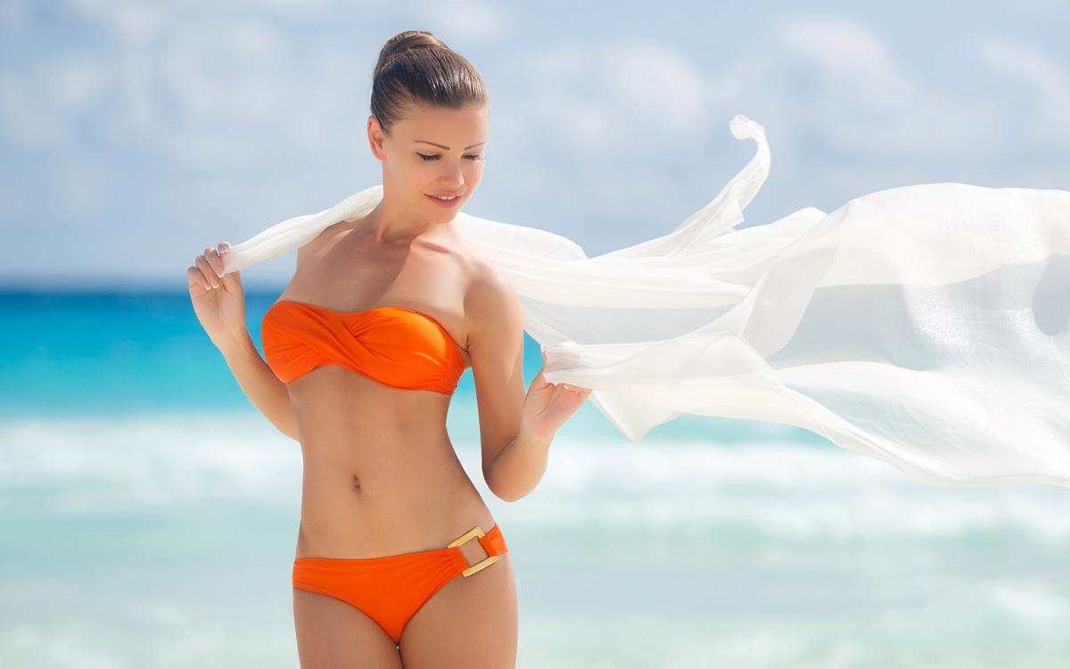 Девушка с парео на пляже.