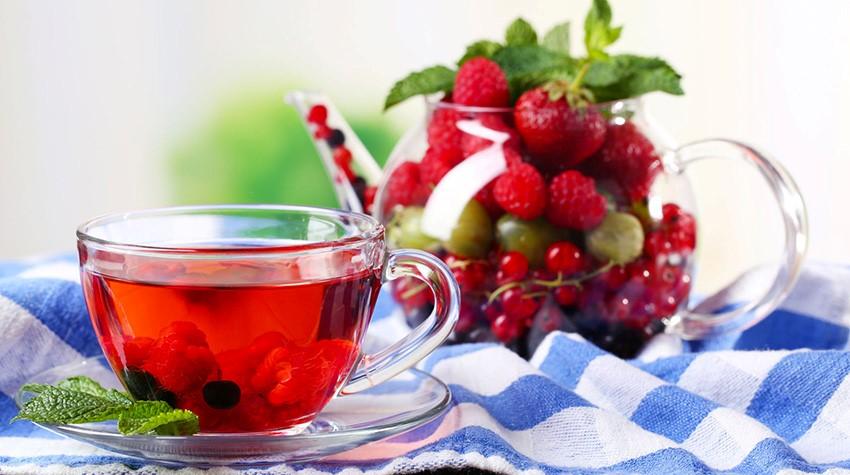 Чашка чаю з малиною і фрукти в заварнику