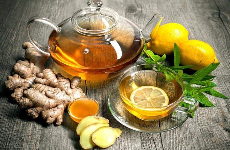 Чай, лимон, мед, имбирь и заварник на столе