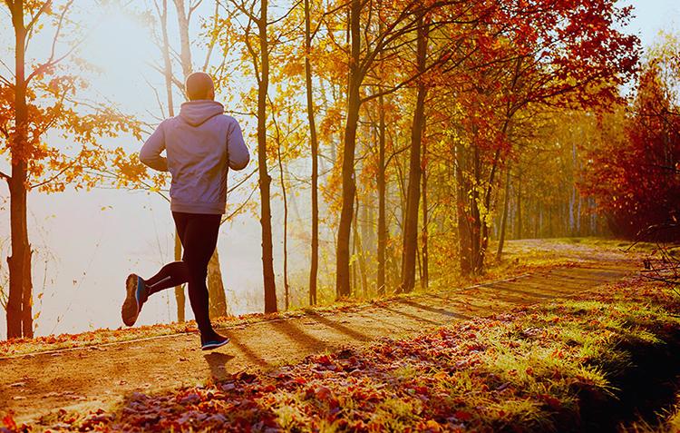 Парень на пробежке в осеннем лесу