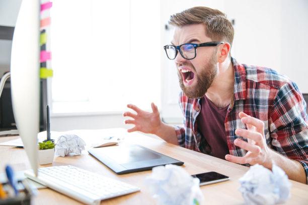 Мужчина в ярости за рабочим столом