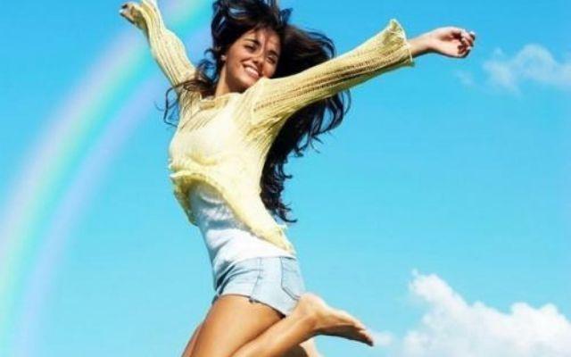 Веселая девушка в прыжке на фоне голубого неба с радугой