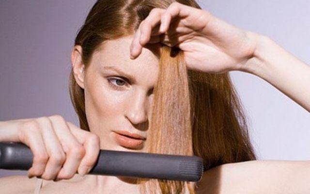 Девушка проводит утюжком по своим волосам