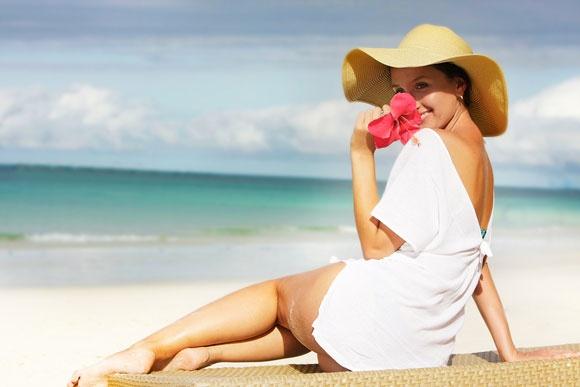 Девушка в шляпе с цветком в руках на берегу моря