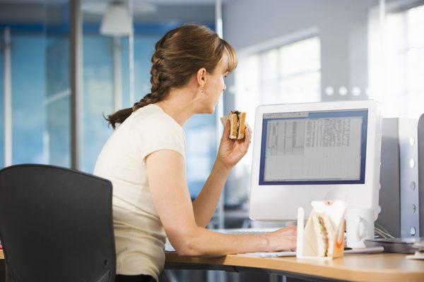 Девушка с сендвичем на рабочем месте