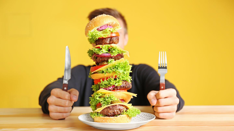 Великий бургер і чоловік з ножем і виделкою