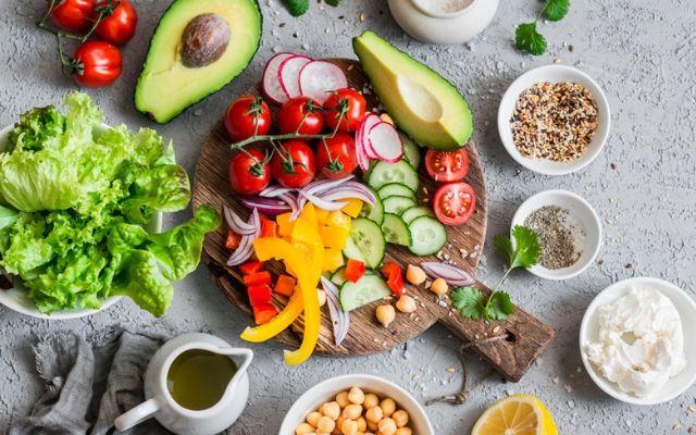 Овощное ассорти на деревяной доске, авокадо, растительное масло, салат листовой