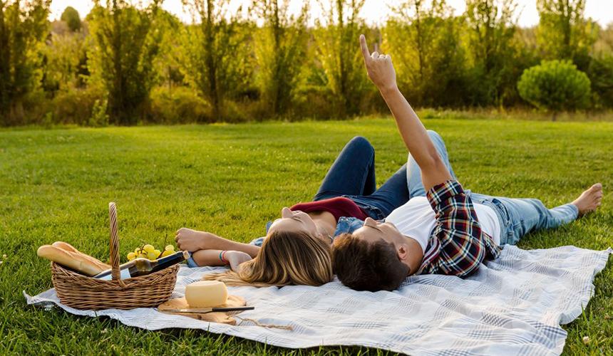 Дівчина з хлопцем на пікніку лежать на покривалі дивлячись у небо