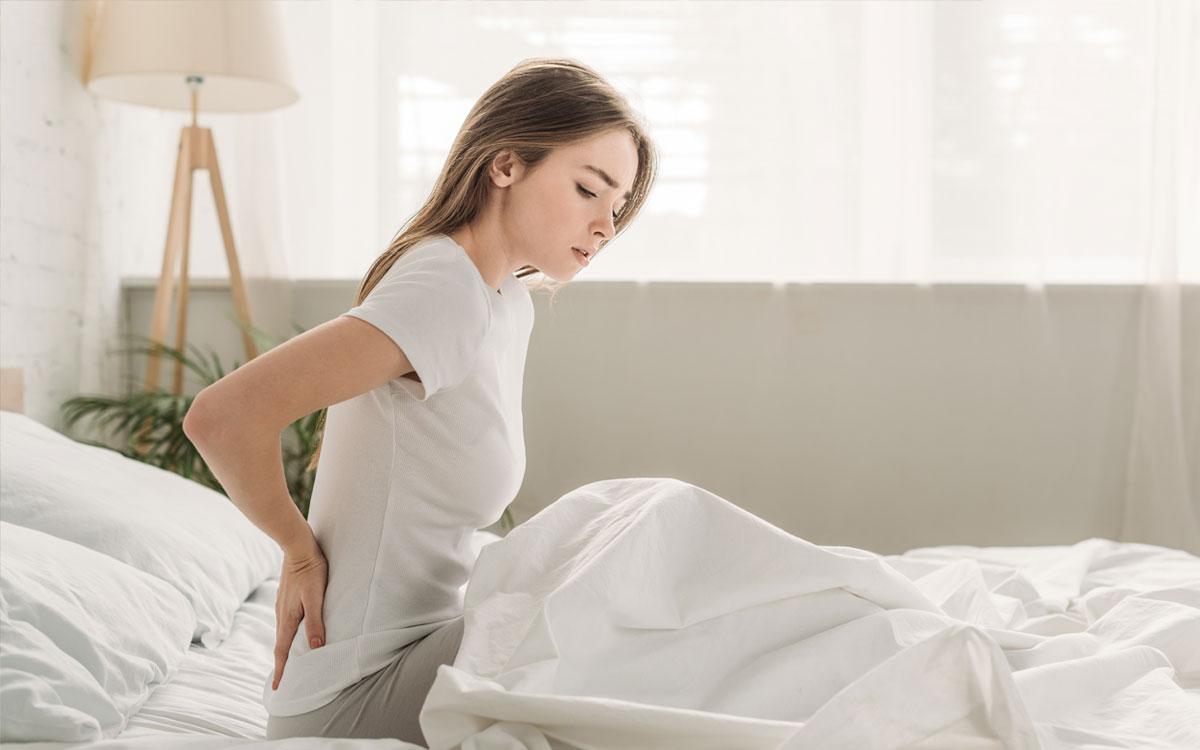 Девушка в кровати с болью в пояснице