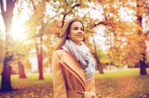 Дівчина в осінньому парку на сонячній прогулянці