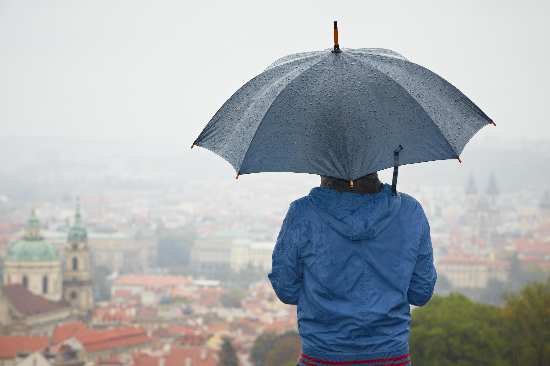 Людина під дощем з парасолькою дивиться на місто