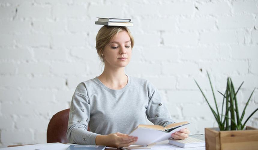 Девушка сидя читает книгу и держит две книги на голове