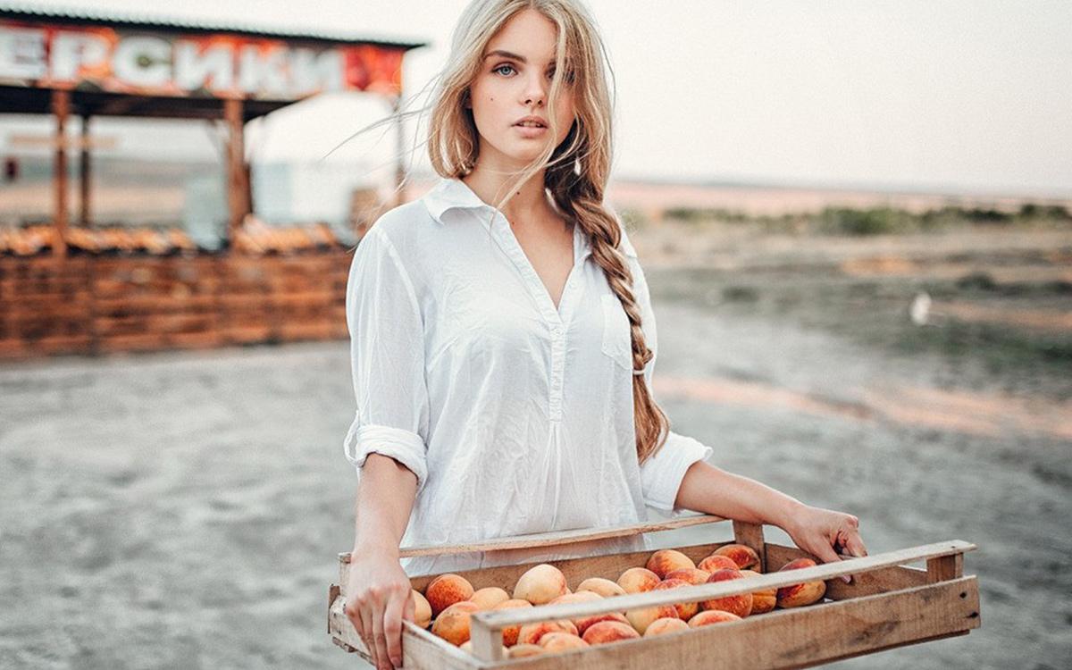 Дівчина на пляжі з персиками