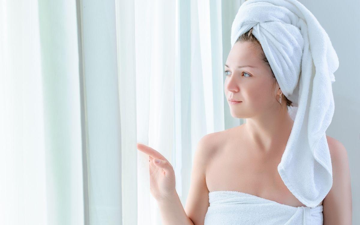 Девушка в полотенце смотрит в окно