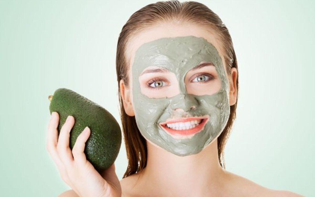 Девушка с косметической маской на лице и авокадо в руке