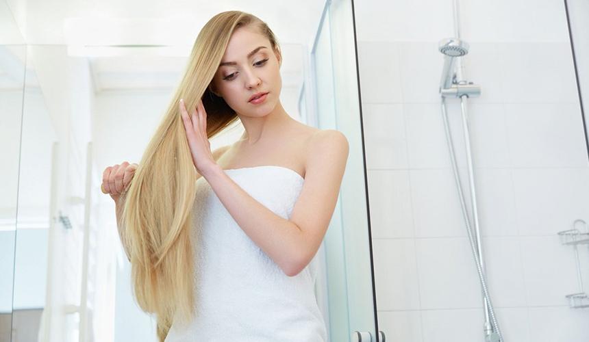 Девушка расчесывает красивые длинные волосы после водных процедур