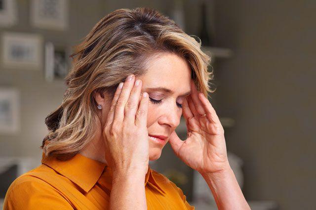 Женщина держит руки у весков от головной боли