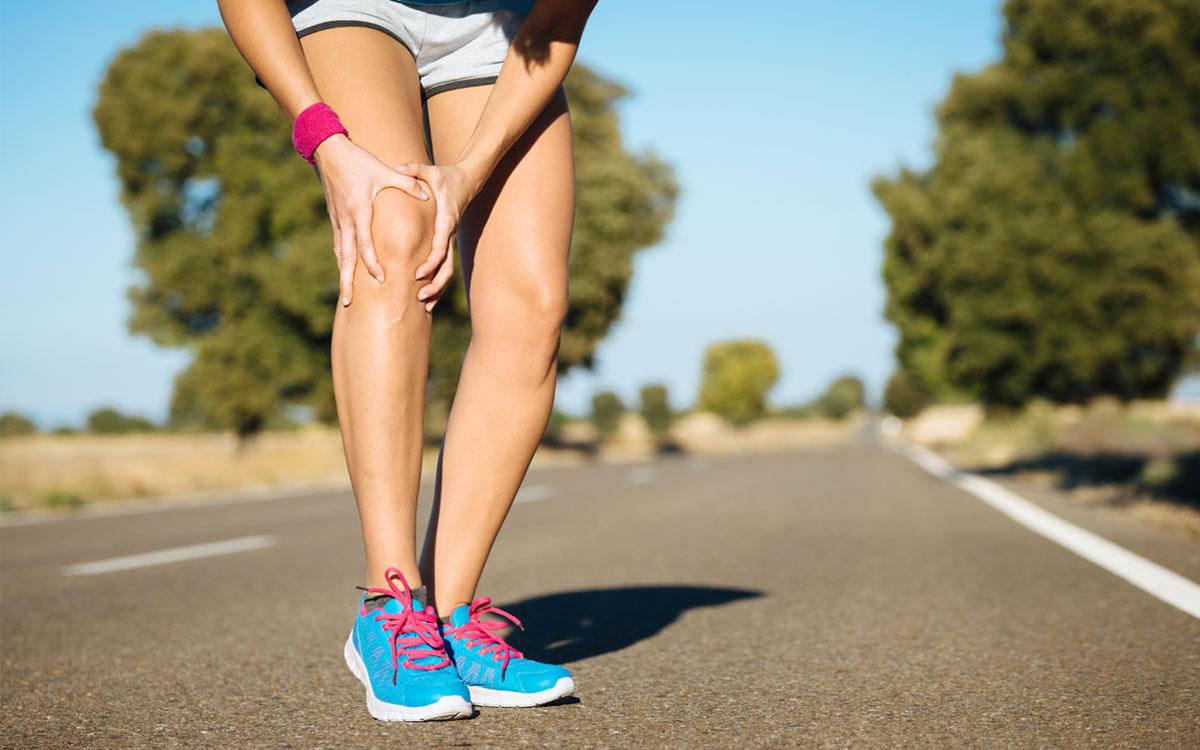 Дівчина на пробіжці тримається за коліно
