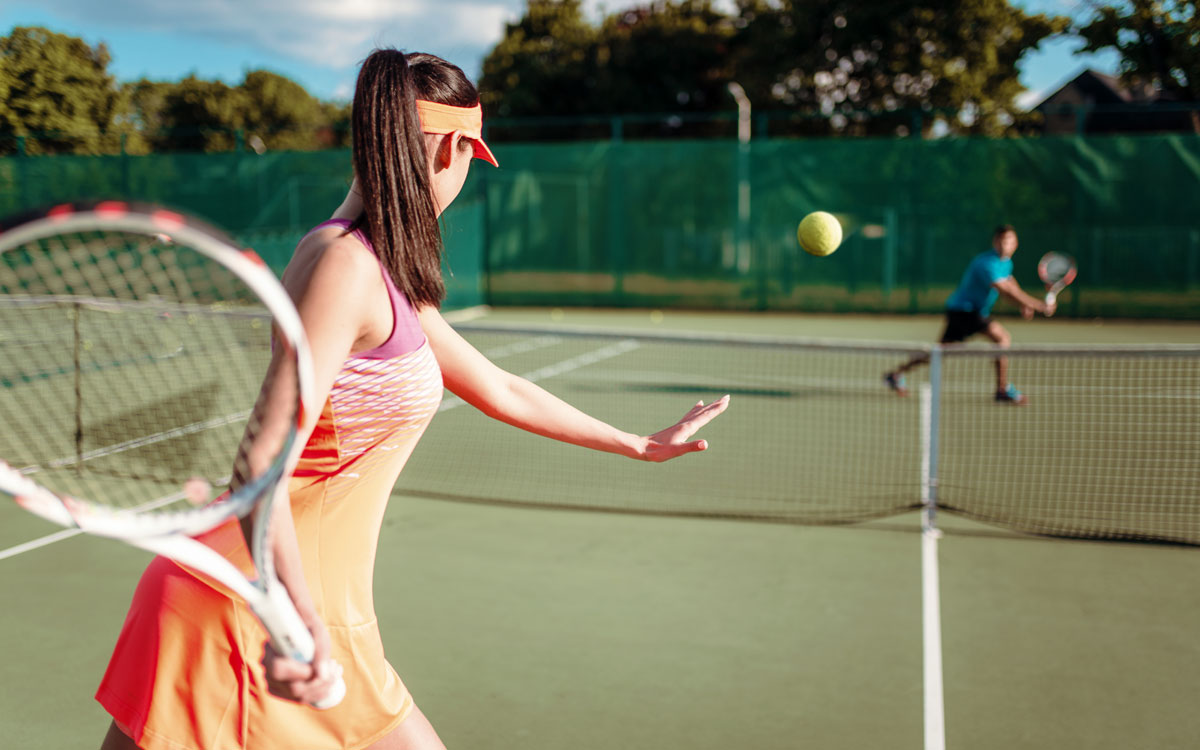 Девушка и парень играют в большой тенис