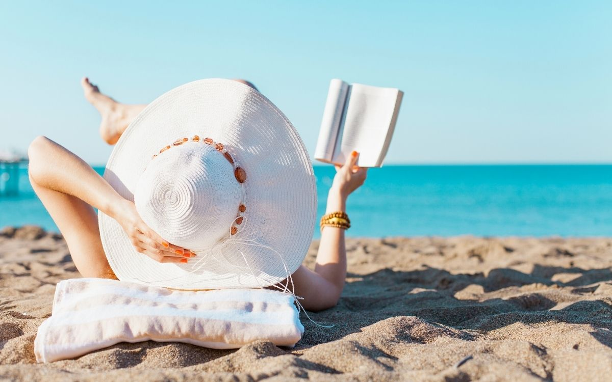 Девушка загорает на пляже с книгой в руках