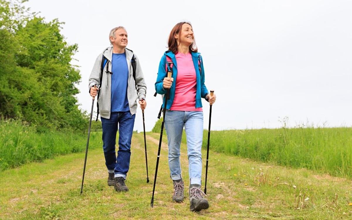 Женщина и мужчина занимаются скандинавской ходьбой