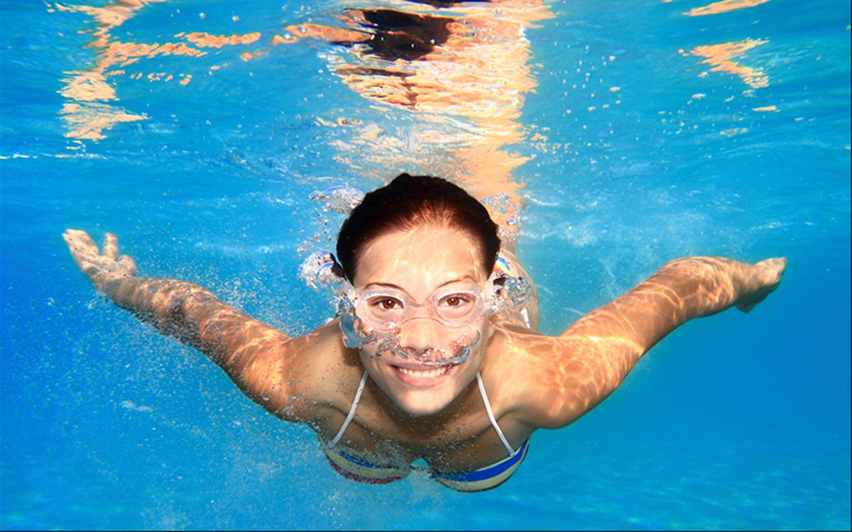 Девушка плавает в бассейне