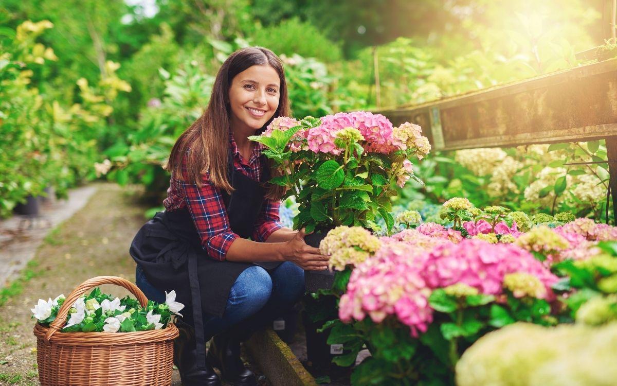 Дівчина доглядає за квітами в саду